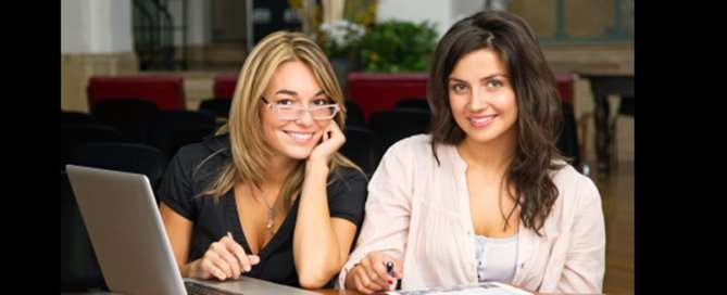 Two female friends studying together in library