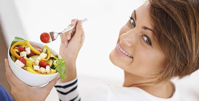 Shot of a cheerful young woman eating a salad