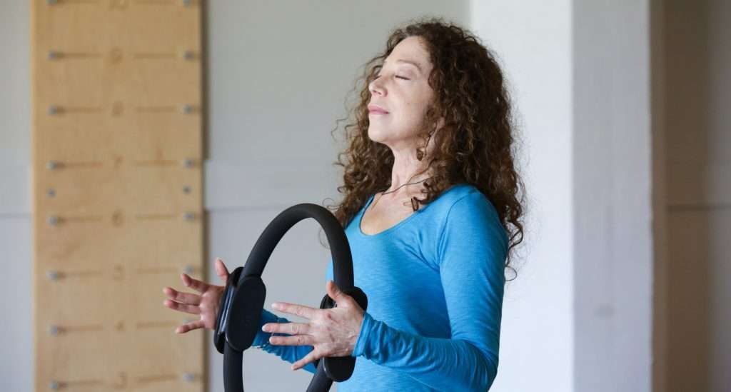 Woman holding Pilates ring and breathing