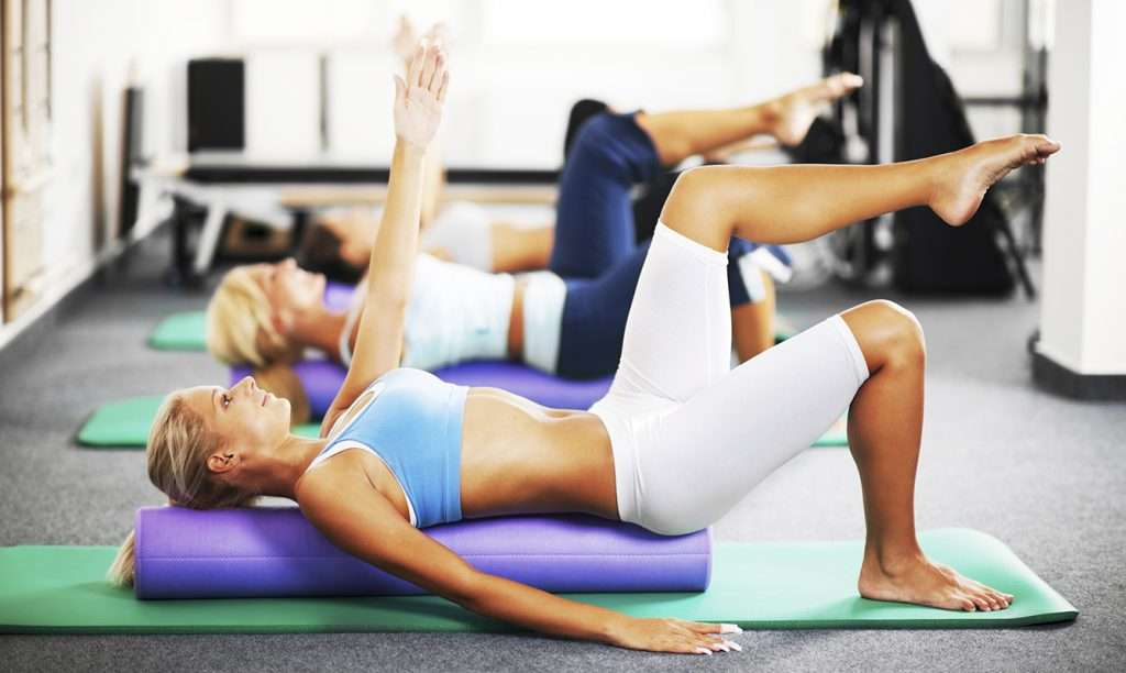 Women doing Pilates exercises using foam Pilates rollers.