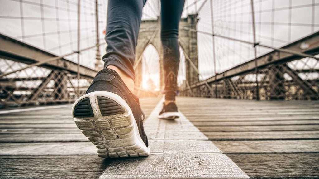 Woman running outdoors - Young sportive girl jogging at sunset on Brooklyn Bridge, close up on shoes