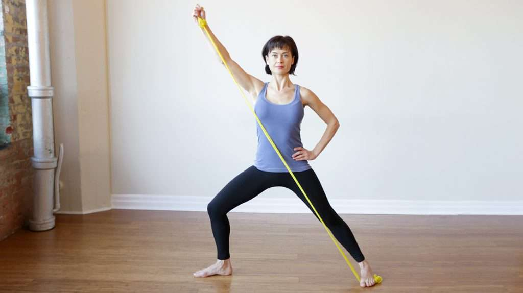 Athletic woman reaching theraband overhead