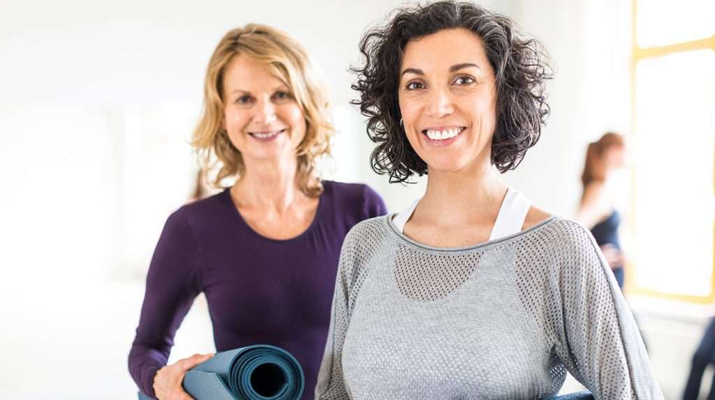 Two mature females holding yoga mat in health club. Fitness women relaxing after yoga class.