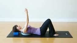 Young woman laying on her back with a balance cushion